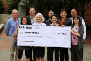 """Intiman Theatre presents """"big"""" donation check to Fred Hutch employees. Photo Credit: Robert Hood / Fred Hutch News Service"""