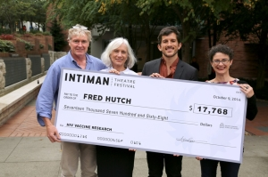 Big check passing from Fred Hutch to Intaman Theater on Oct. 9, 2015.